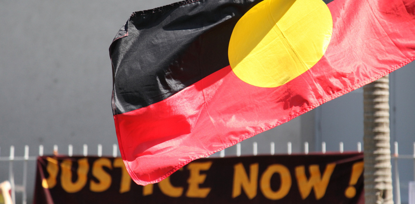Aboriginal flag with justice now sign