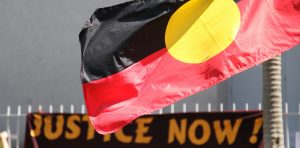 Justice Now sign and Aboriginal flag