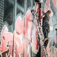 Graffiti sprayer on ladder