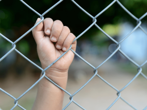Child's hand holding wire in detention