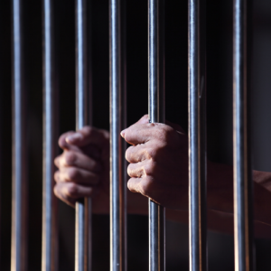 man with hands on prison bars
