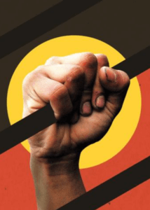 Indigenous hand grips jail bar with backdrop of Aboriginal flag